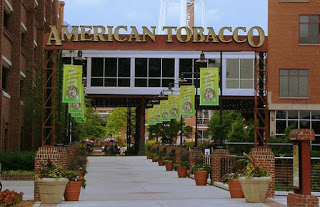 Sidewalk lined with potted plants with American Tobacco Signage on the Skyway
