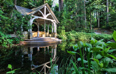 Outdoor pavillion surrounded by trees on behind a pond