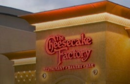 The Cheesecake Factory Restaurant Bakery Bar sign in lighted red letters on the side of a building