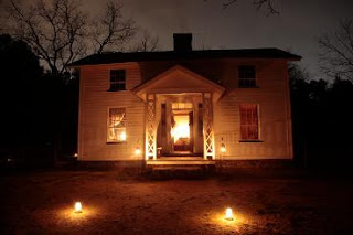 Older house in the dark with light shining from the doorway and lights in the front yard