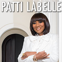 Patti Labelle Woman dressed in white posing in front of a doorway