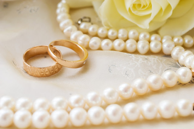 Cream-colored rose, pearl necklace, and two gold wedding bands
