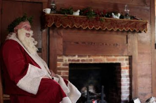 Santa sitting in front of a fireplace
