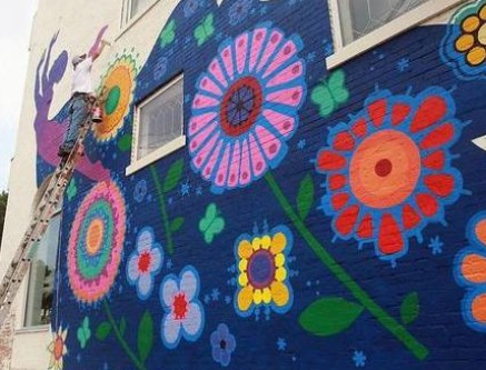 Durham's Ninth Street District side of building being painted with flowers