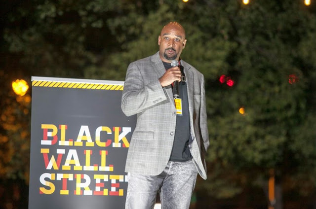 man on stage holding microphone with Black Wall Street banner behind him