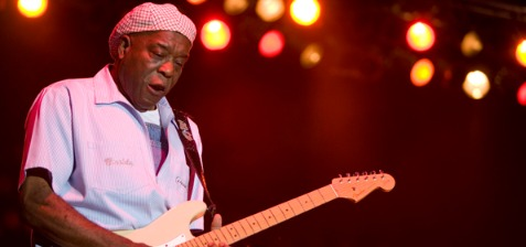 Older African American Gentleman playing a guitar with stage light in the background
