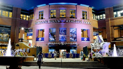 Night View of the brick entrance to the Durham Bulls Athletic Park with water fountains and people standing in the forefront