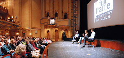 Audience listening to people on stage at the Carolina Theater at full frame documentary film festival