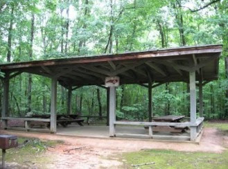 Covered wooden picnic shelter with picnic tables surrounded by leafy green trees