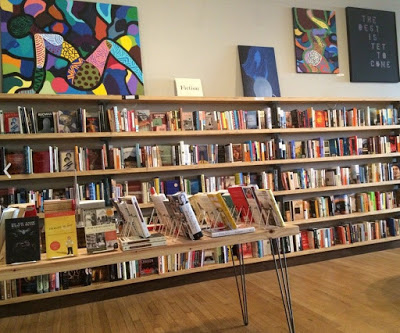 various books on shelves and tabletop with colorful abstract art hanging above on the wall
