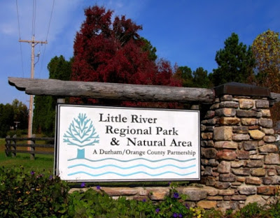 Little river regional park and natural area sign with a blue sky and trees with red, green and yellow leaves in the background