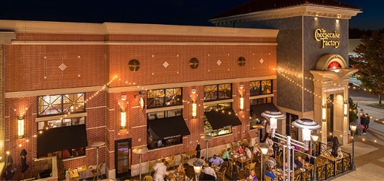 Outside view of the Cheesecake factory at night with people eating on the restaurant patio