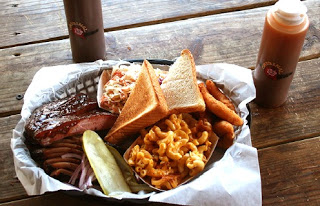 a basket with macaroni and cheese, barbeque ribs, cole slaw, texas toast, pickle and hush puppies on a wooden table with hot sauce bottles