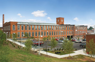 Large three story Brick building with glass window with parking lot and cars in the forefront