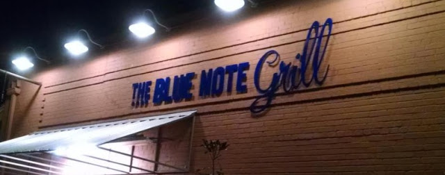The Blue Note Grill building with bright lights shining at night