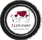 Zinburger Wine & Burger Bar logo in a circle with a red spotted cow drinking from a glass of wine