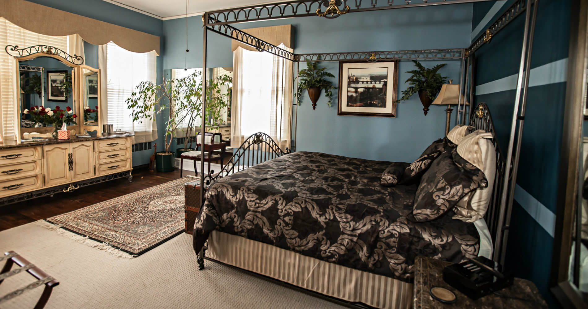 view of a king sized wrought iron canopy bed with brown comforter