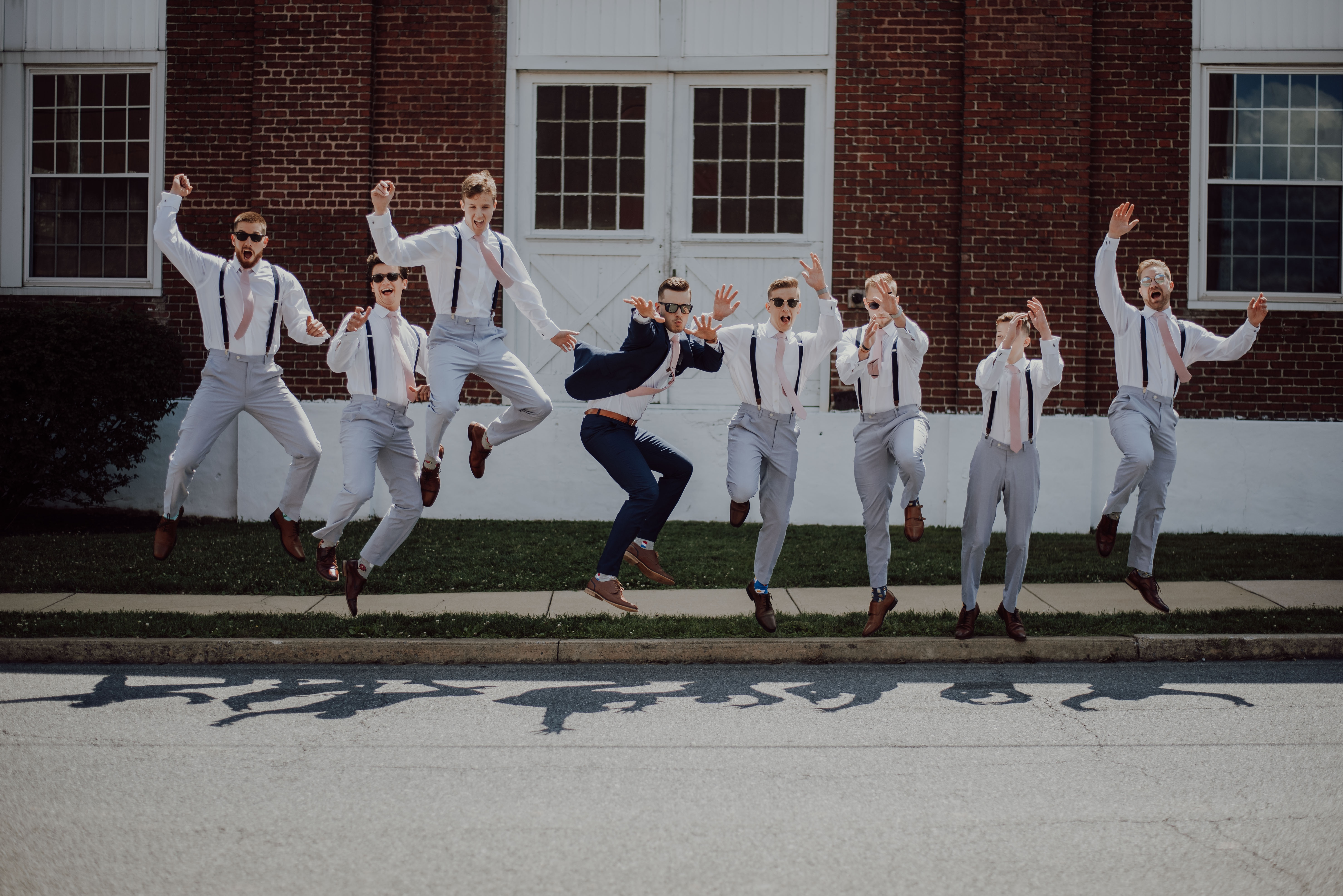 Groom celebrating with his groomsmen, cheerfully jumping off the street curb in