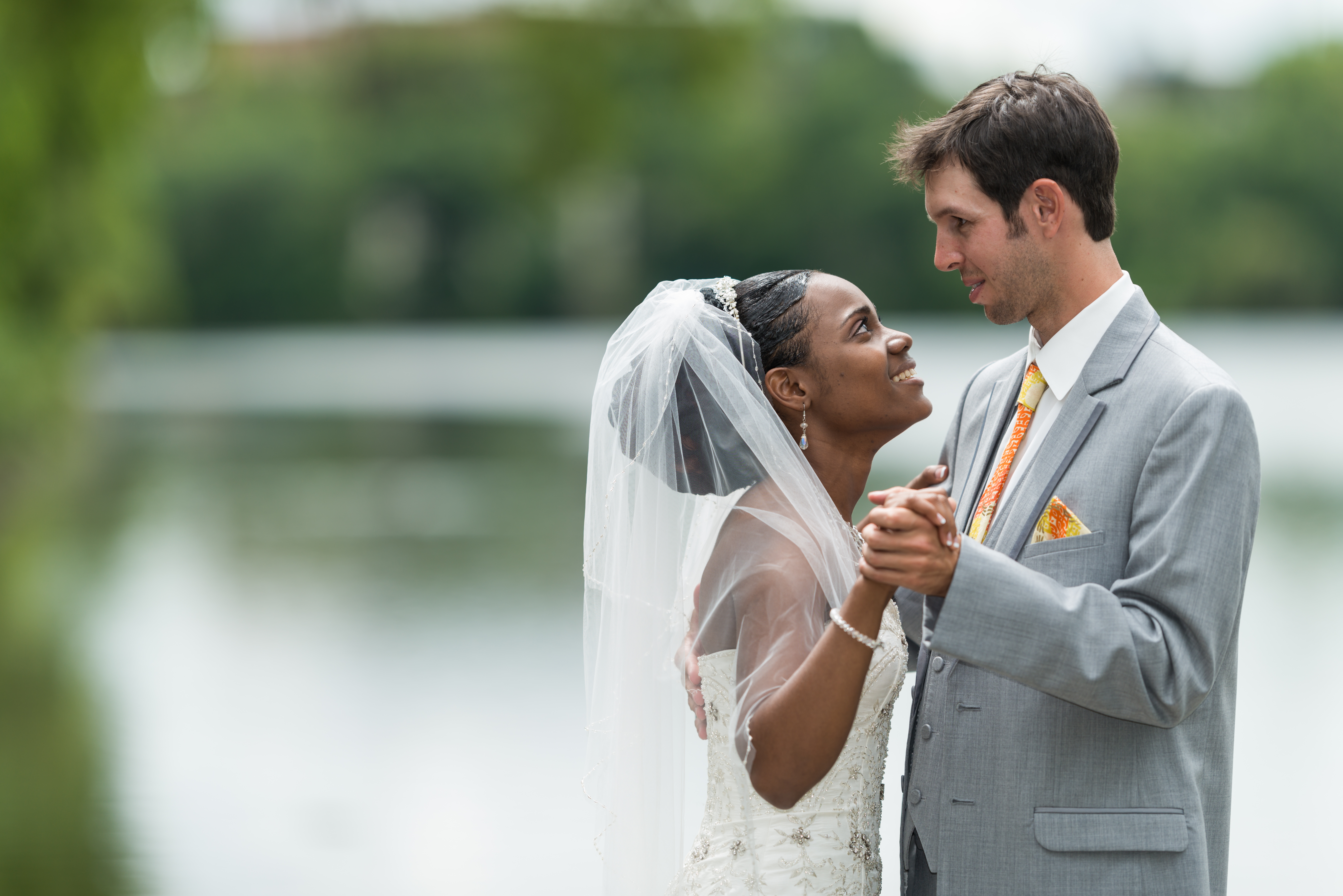 Bride and groom looking into one another's eyes in front of a lake